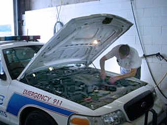 Man working on a police car under the hood.