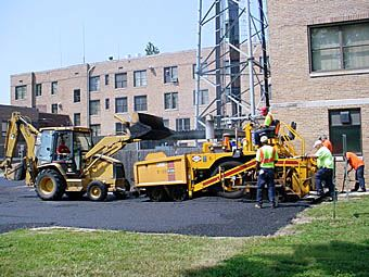 A group of men using equipment in a parking lot.